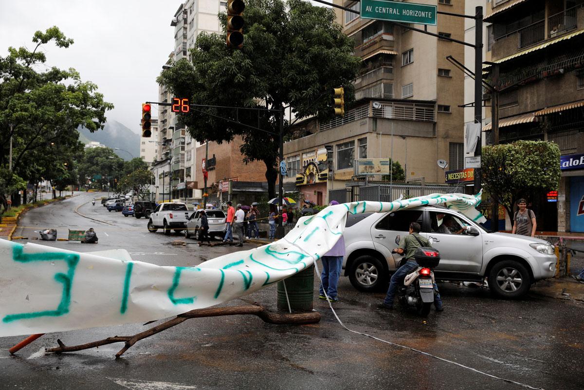 A car and a motorcyclist pass through a barricade during a rally against Venezuelan President Nicolas Maduro's government in Caracas, Venezuela, July 19, 2017.  REUTERS/Carlos Garcia Rawlins