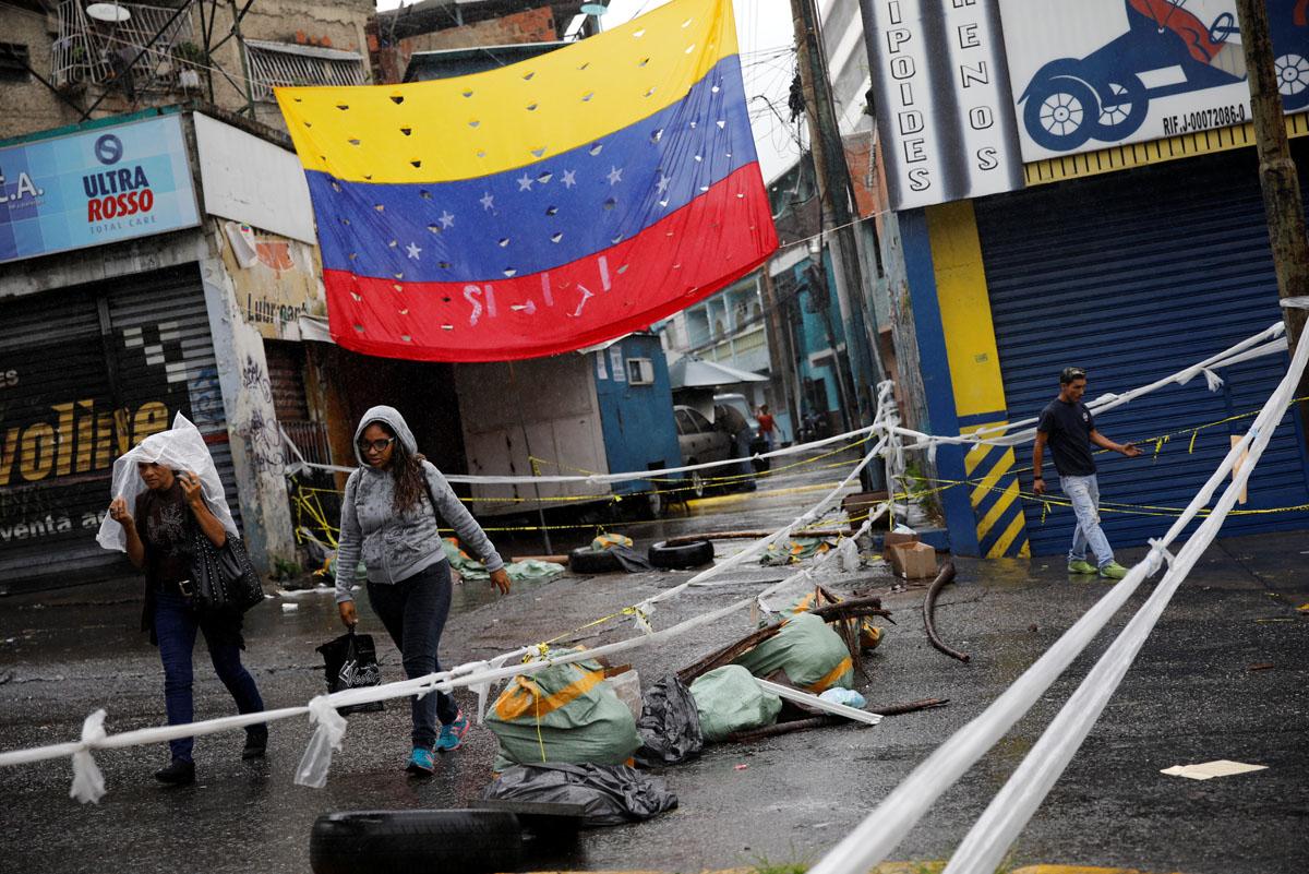Pedestrians walk past a barricade during a rally against Venezuelan President Nicolas Maduro's government in Caracas, Venezuela, July 19, 2017.  REUTERS/Carlos Garcia Rawlins
