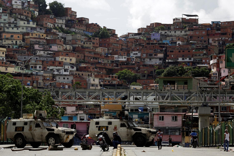 La gente pasa por una calle bloqueada por las fuerzas de seguridad durante una huelga convocada para protestar contra el gobierno del presidente venezolano Nicolás Maduro en Caracas, Venezuela, 20 de julio de 2017. REUTERS / Marco Bello