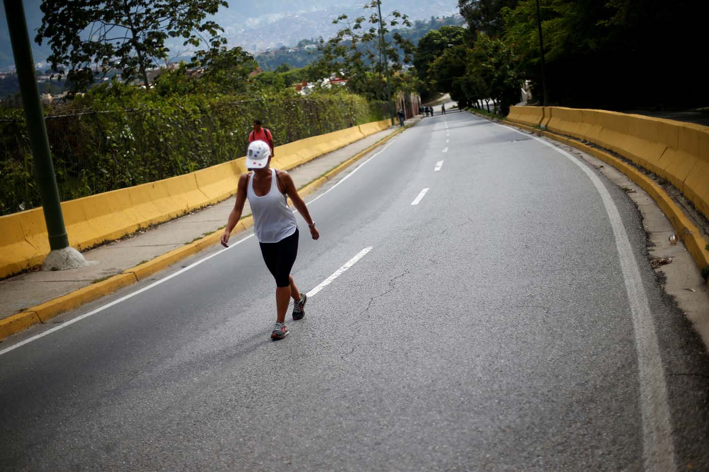 A woman walks along a street during a strike called to protest against Venezuelan President Nicolas Maduro's government in Caracas, Venezuela July 26, 2017. REUTERS/Andres Martinez Casares