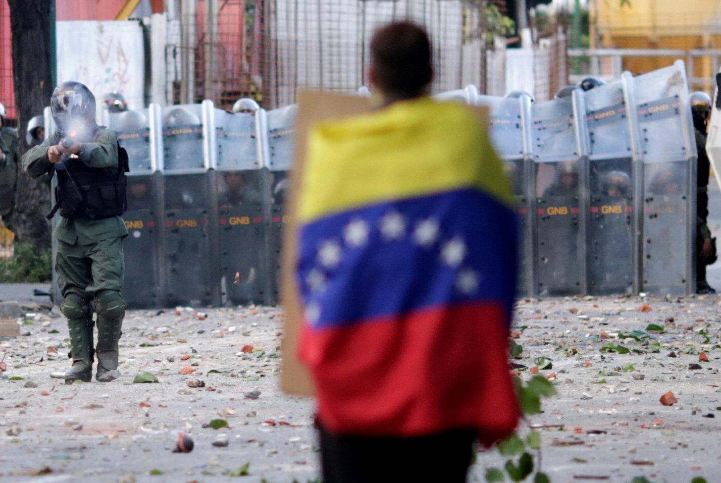 Un hombre con bandera venezolana se alza frente a las fuerzas de seguridad antidisturbios mientras se reúne contra el gobierno del presidente de Venezuela, Nicolás Maduro, en Caracas, Venezuela, el 26 de julio de 2017. REUTERS/Ueslei Marcelino