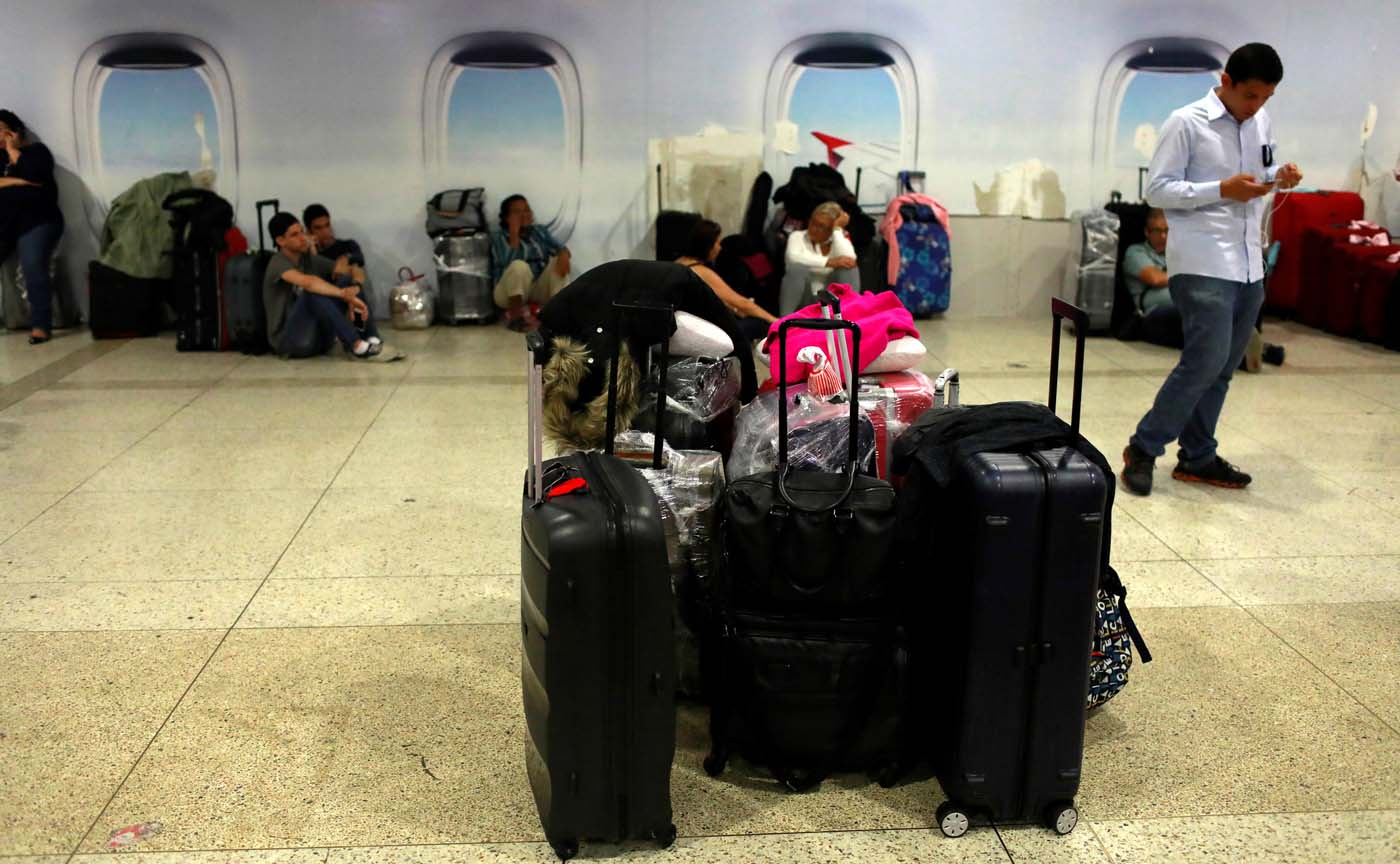 People wait by a counter of Avianca airline, at the Simon Bolivar airport in Caracas, Venezuela July 27, 2017. REUTERS/Marco Bello