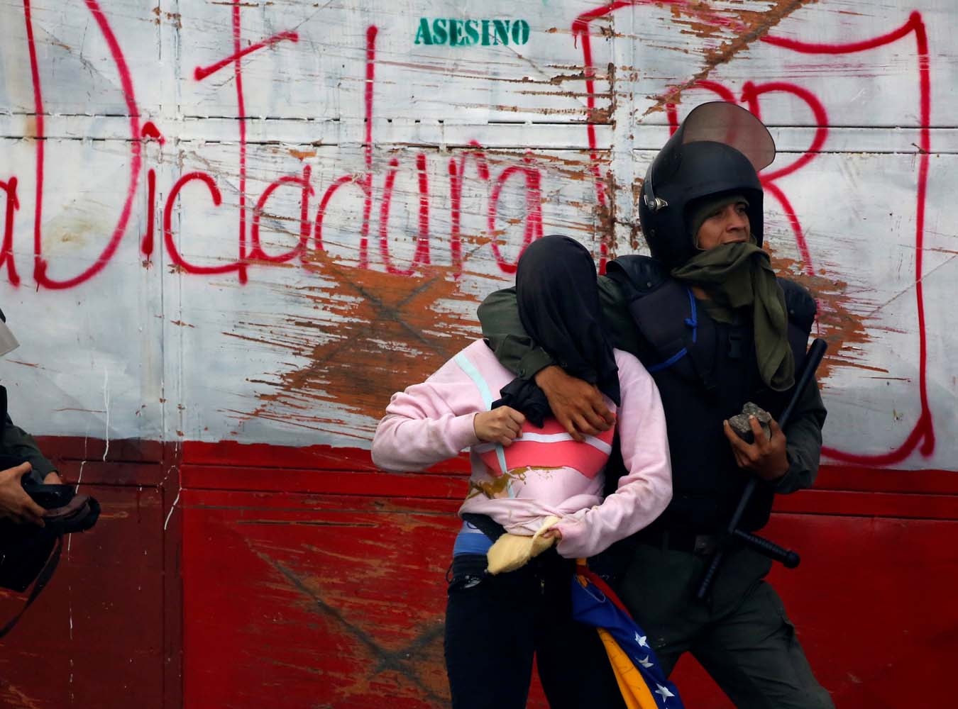"""Riot security forces detain a demonstrator during a rally against Venezuela's President Nicolas Maduro's government in Caracas, Venezuela, July 28, 2017. The graffiti on the back reads """"Dictatorship"""". REUTERS/Carlos Garcia Rawlins"""