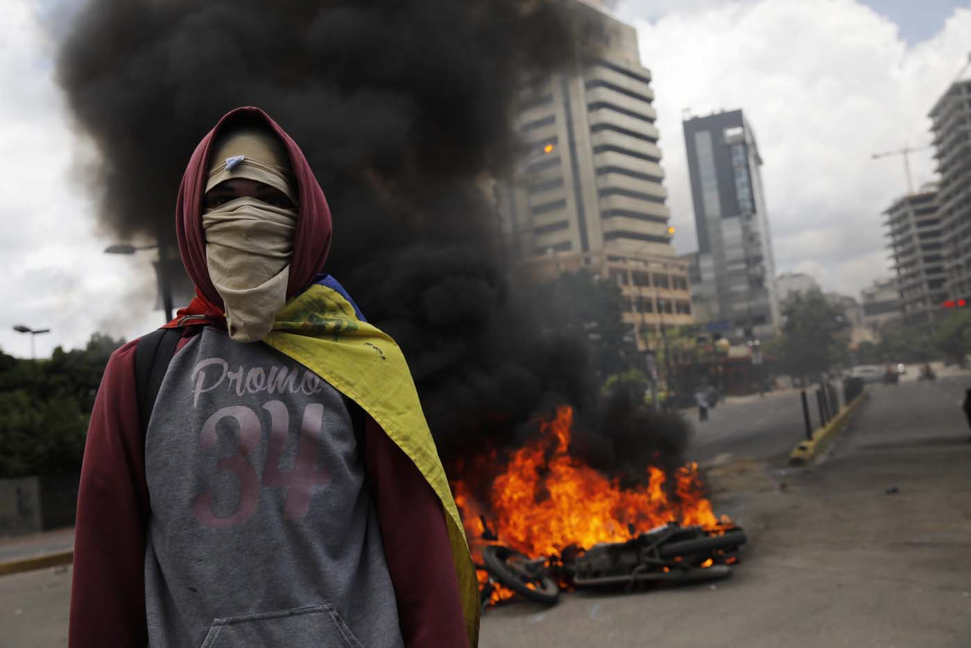 An opposition supporter walks near burning motorcycles as clashes break out while the Constituent Assembly election is being carried out in Caracas, Venezuela, July 30, 2017. REUTERS/Carlos Garcia Rawlins