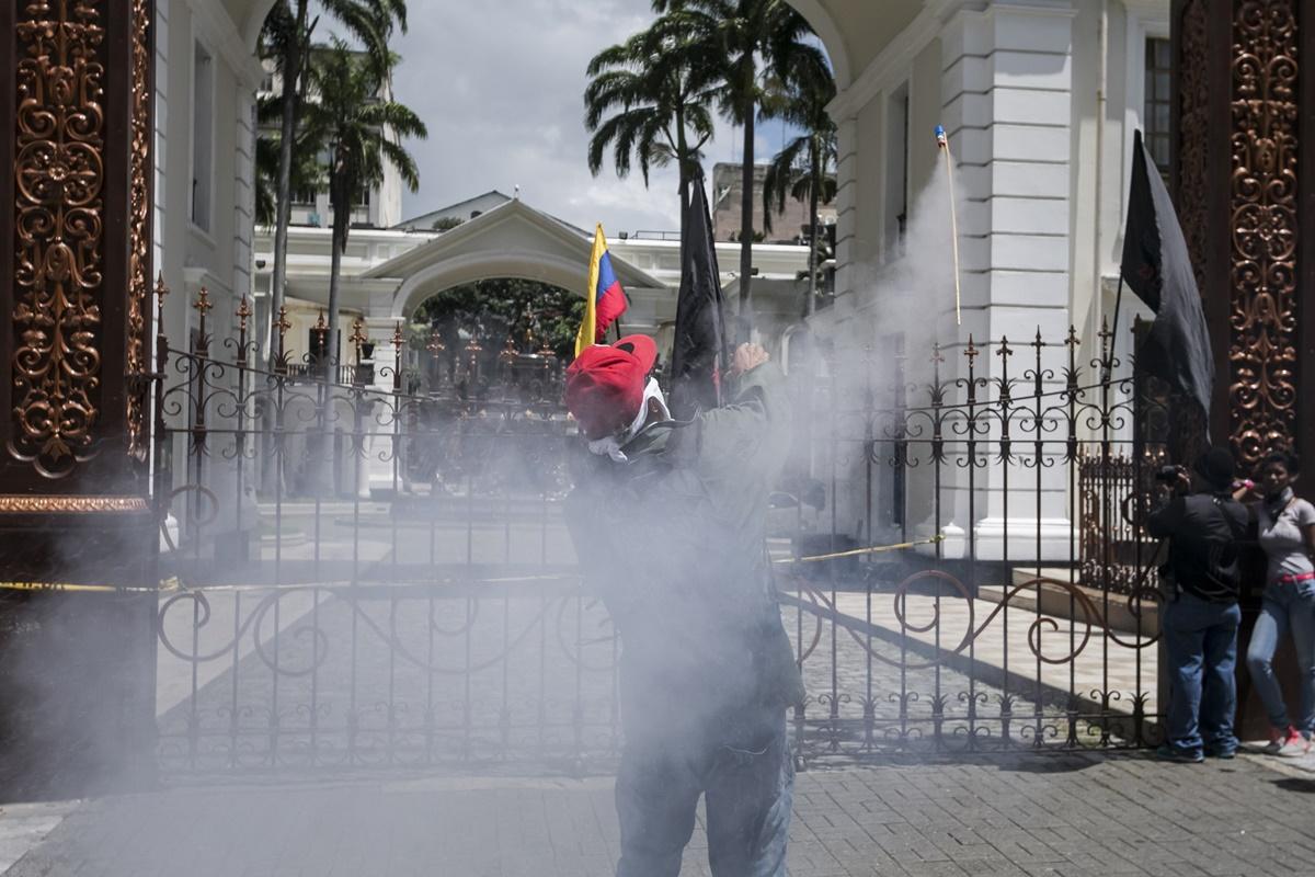 CAR16 - CARACAS (VENEZUELA), 05/07/2017 - Un simpatizante del Gobierno lanza un cohete pirotécnico hacia el edificio de la Asamblea Nacional hoy, miércoles 5 de mayo de 2017, en Caracas (Venezuela). Un grupo de simpatizantes del Gobierno venezolano irrumpió hoy por la fuerza en la Asamblea Nacional (AN, Parlamento), de mayoría opositora, y causaron heridas a algunos diputados que se encontraban en el recinto para una sesión en conmemoración del Día de la Independencia en el país. EFE/MIGUEL GUTIÉRREZ