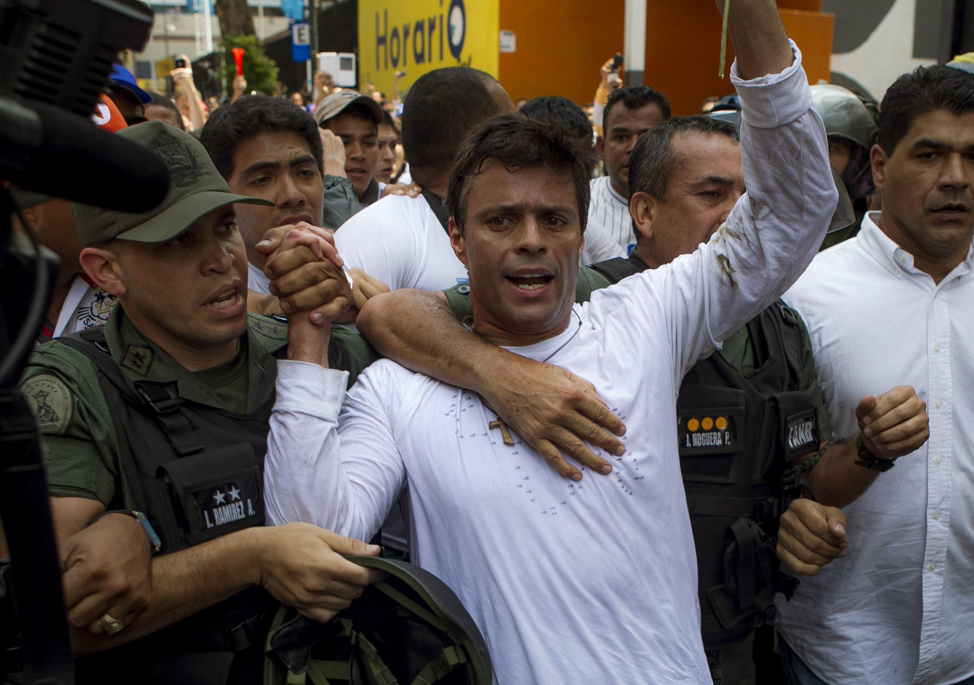 """GRA190. CARACAS, 08/07/2017.- Fotografía de archvivo (Caracas, 18/02/2014), del opositor venezolano Leopoldo López cuando se entregó a miembros de la Guardia Nacional (GNB, policía militarizada) en una plaza en Caracas (Venezuela). Leopoldo López ha abandonado la cárcel y ha pasado a estar en una situación de """"arresto domiciliario"""". Según su abogado español Javier Cremades en un tuit hecho público hoy, el opositor """"aún no es libre"""", pero ya """"está en su casa con su mujer y sus hijos"""". EFE/MIGUEL GUTIERREZ"""