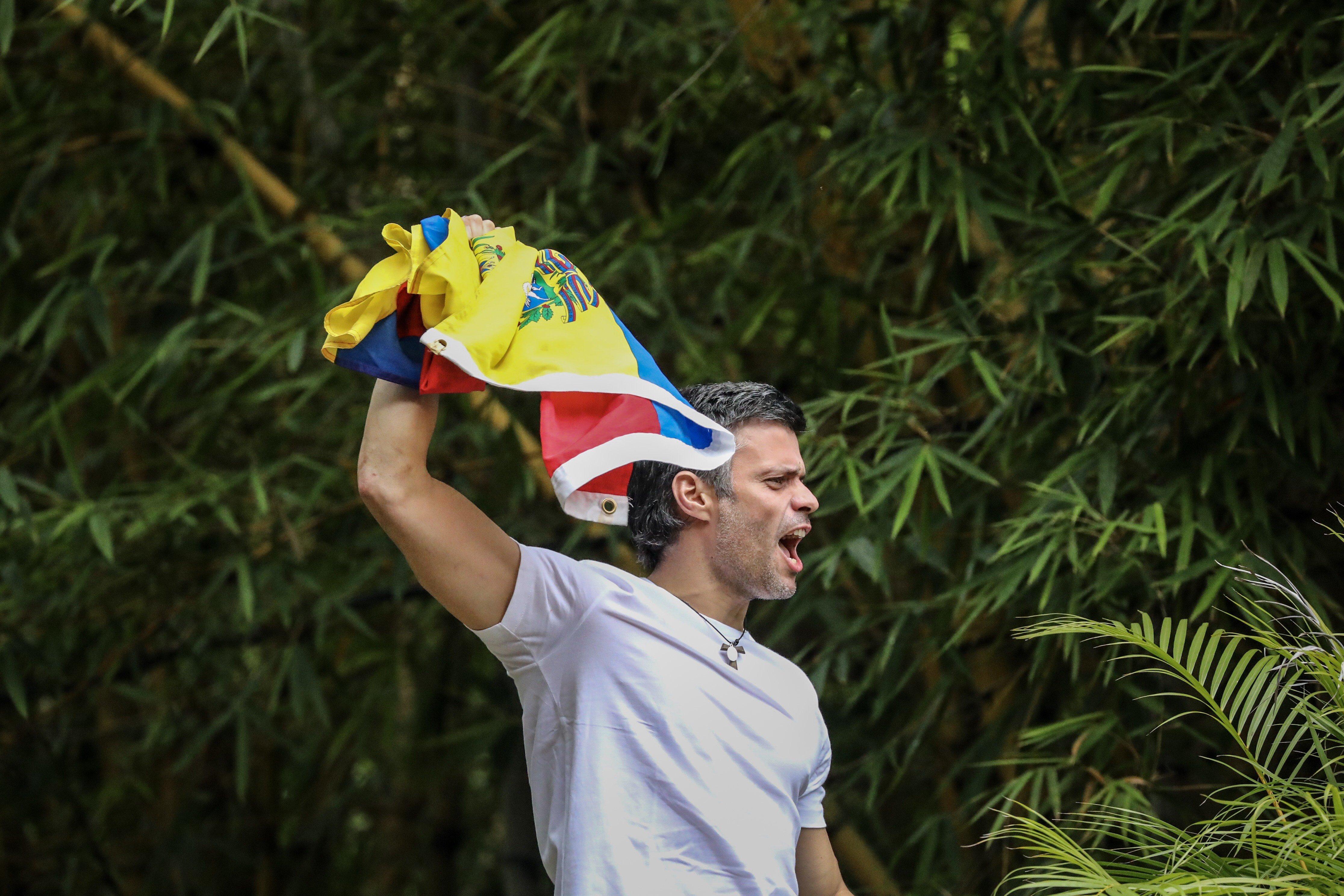 CAR28. CARACAS (VENEZUELA), 08/07/2017.- El opositor venezolano Leopoldo López saluda a seguidores hoy, sábado 8 de julio de 2017, en la entrada de su casa en Caracas (Venezuela). Leopoldo López saludó hoy desde dentro de su residencia en Caracas a la que llegó esta madrugada tras recibir una medida de arresto domiciliario que le sacó de la prisión militar en la que estaba recluido desde febrero de 2014, con una condena de 14 años de cárcel. EFE/MIGUEL GUTIÉRREZ