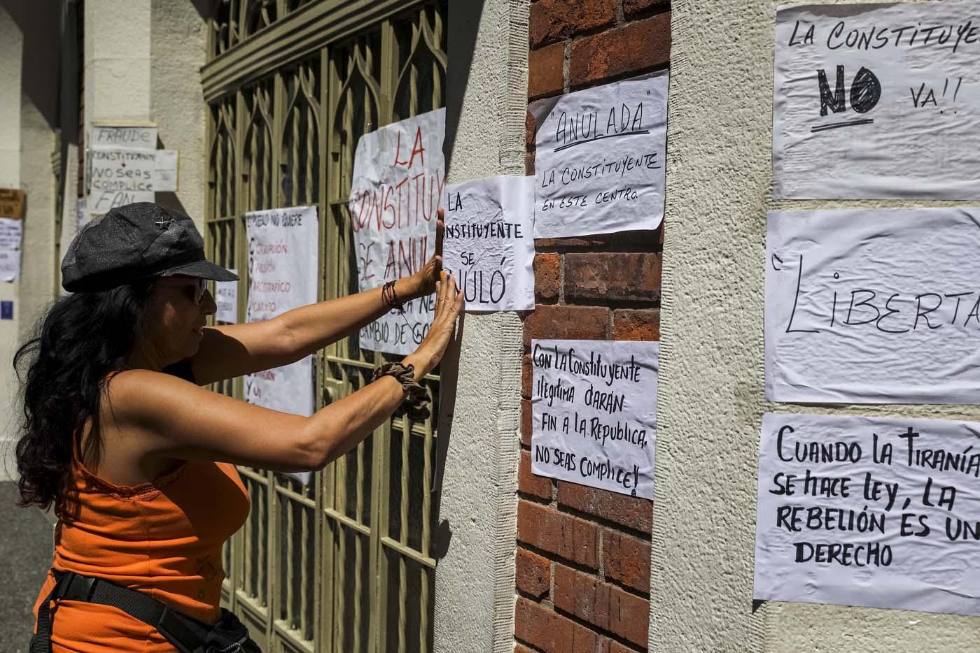 CAR02. CARACAS (VENEZUELA), 24/07/2017.- Una mujer pega carteles en rechazo a la Asamblea Constituyente hoy, lunes 24 de julio de 2017, en una verja de Caracas (Venezuela). Venezuela inicia hoy la semana decisiva para la elección de la Asamblea Nacional Constituyente convocada por el presidente, Nicolás Maduro, con los oficialistas entrando en la recta final de su campaña en medio de protestas y llamados a paro de los opositores en rechazo a esos comicios. EFE/Miguel Gutiérrez