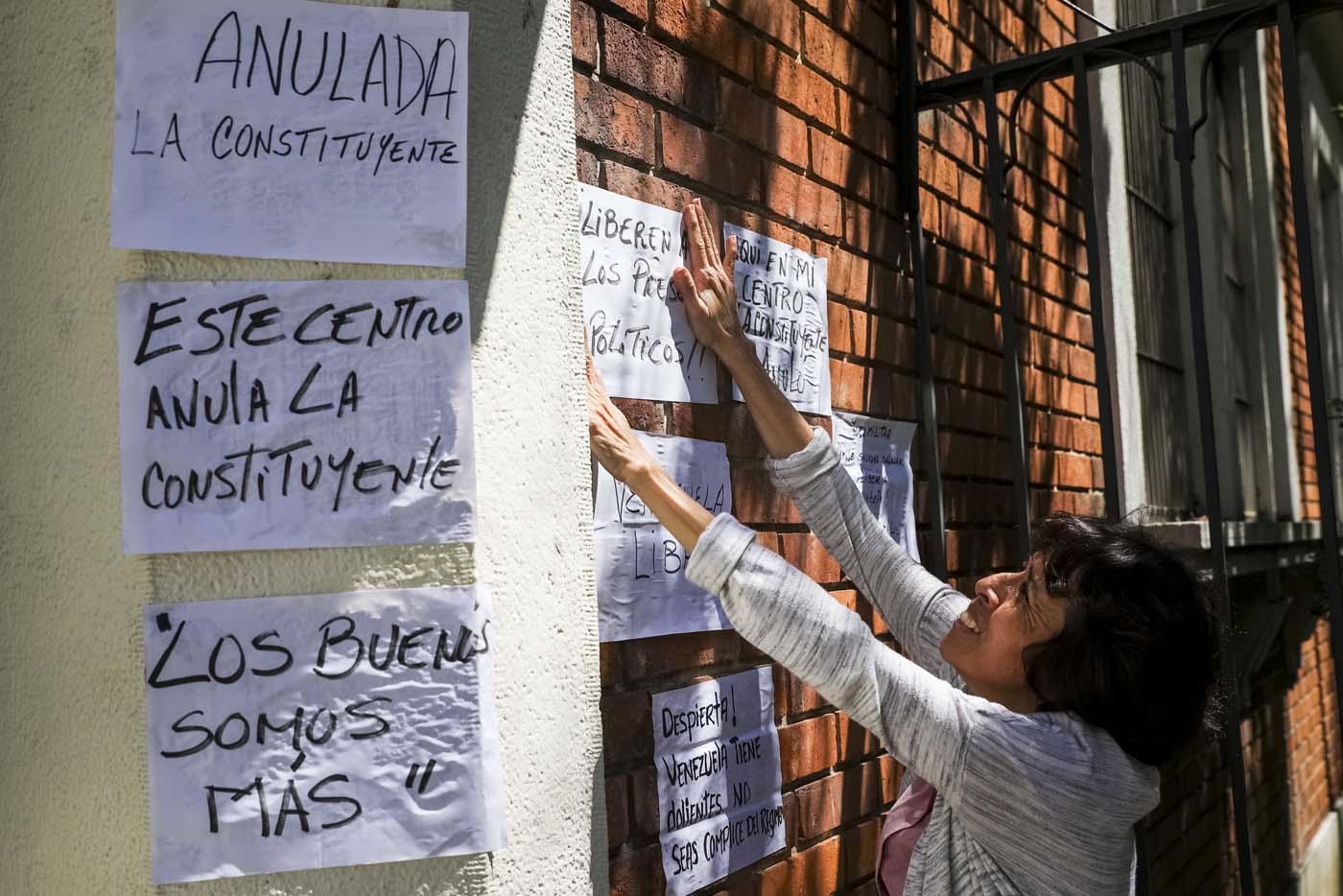 CAR03. CARACAS (VENEZUELA), 24/07/2017.- Una mujer pega carteles en rechazo a la Asamblea Constituyente hoy, lunes 24 de julio de 2017, en una verja de Caracas (Venezuela). Venezuela inicia hoy la semana decisiva para la elección de la Asamblea Nacional Constituyente convocada por el presidente, Nicolás Maduro, con los oficialistas entrando en la recta final de su campaña en medio de protestas y llamados a paro de los opositores en rechazo a esos comicios. EFE/Miguel Gutiérrez