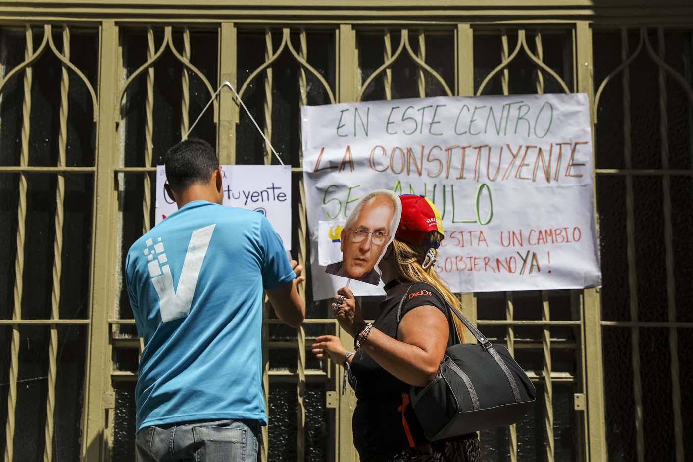 CAR06. CARACAS (VENEZUELA), 24/07/2017.- Una pareja pega carteles en rechazo a la Asamblea Constituyente hoy, lunes 24 de julio de 2017, en un colegio electoral de Caracas (Venezuela). Venezuela inicia hoy la semana decisiva para la elección de la Asamblea Nacional Constituyente convocada por el presidente, Nicolás Maduro, con los oficialistas entrando en la recta final de su campaña en medio de protestas y llamados a paro de los opositores en rechazo a esos comicios. EFE/Miguel Gutiérrez