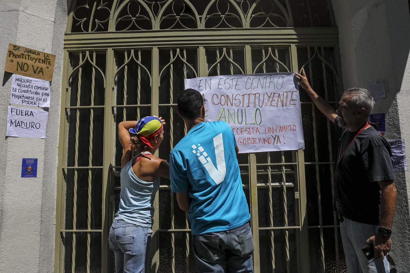 CAR09. CARACAS (VENEZUELA), 24/07/2017.- Manifestantes pegan carteles en rechazo a la Asamblea Constituyente hoy, lunes 24 de julio de 2017, en un colegio electoral de Caracas (Venezuela). Venezuela inicia hoy la semana decisiva para la elección de la Asamblea Nacional Constituyente convocada por el presidente, Nicolás Maduro, con los oficialistas entrando en la recta final de su campaña en medio de protestas y llamados a paro de los opositores en rechazo a esos comicios. EFE/Miguel Gutiérrez