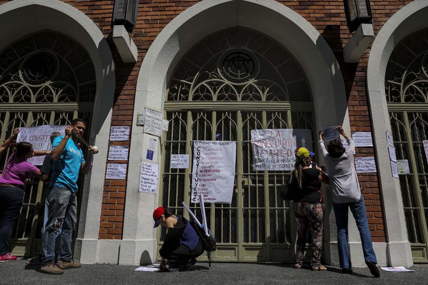 CAR10. CARACAS (VENEZUELA), 24/07/2017.- Manifestantes pegan carteles en rechazo a la Asamblea Constituyente hoy, lunes 24 de julio de 2017, en un colegio electoral de Caracas (Venezuela). Venezuela inicia hoy la semana decisiva para la elección de la Asamblea Nacional Constituyente convocada por el presidente, Nicolás Maduro, con los oficialistas entrando en la recta final de su campaña en medio de protestas y llamados a paro de los opositores en rechazo a esos comicios. EFE/Miguel Gutiérrez