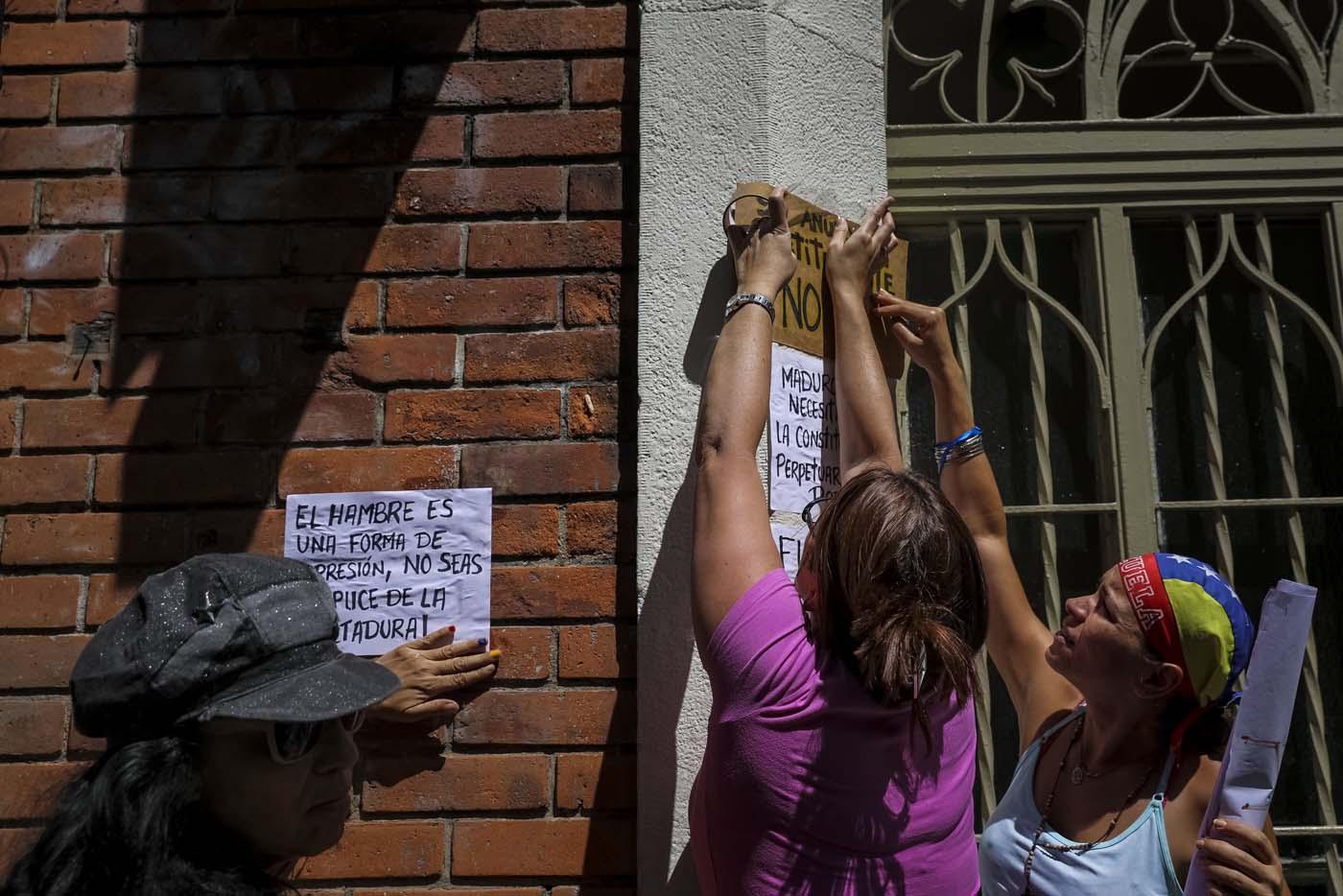 CAR11. CARACAS (VENEZUELA), 24/07/2017.- Manifestantes pegan carteles en rechazo a la Asamblea Constituyente hoy, lunes 24 de julio de 2017, en un colegio electoral de Caracas (Venezuela). Venezuela inicia hoy la semana decisiva para la elección de la Asamblea Nacional Constituyente convocada por el presidente, Nicolás Maduro, con los oficialistas entrando en la recta final de su campaña en medio de protestas y llamados a paro de los opositores en rechazo a esos comicios. EFE/Miguel Gutiérrez