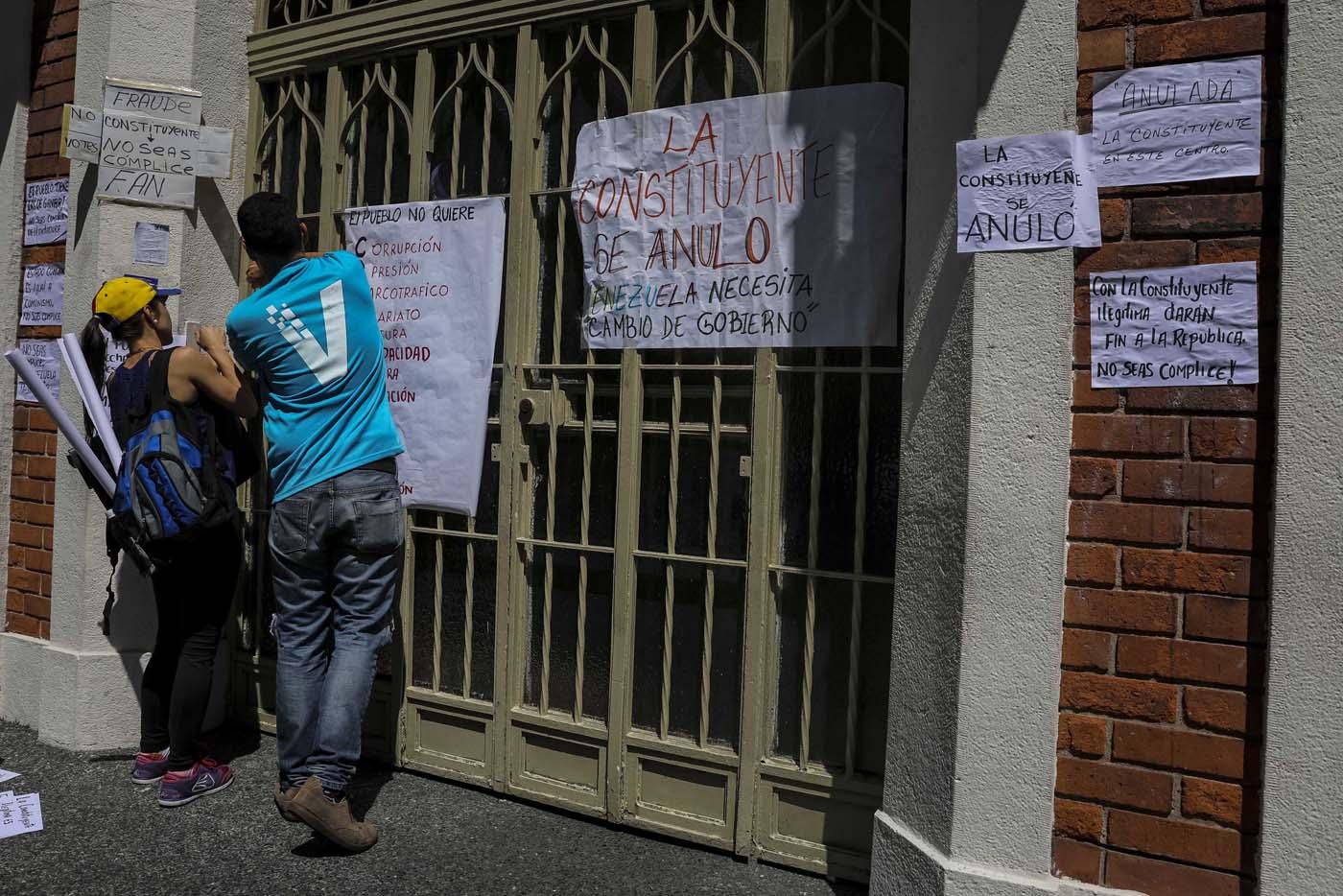 CAR12. CARACAS (VENEZUELA), 24/07/2017.- Manifestantes pegan carteles en rechazo a la Asamblea Constituyente hoy, lunes 24 de julio de 2017, en un colegio electoral de Caracas (Venezuela). Venezuela inicia hoy la semana decisiva para la elección de la Asamblea Nacional Constituyente convocada por el presidente, Nicolás Maduro, con los oficialistas entrando en la recta final de su campaña en medio de protestas y llamados a paro de los opositores en rechazo a esos comicios. EFE/Miguel Gutiérrez