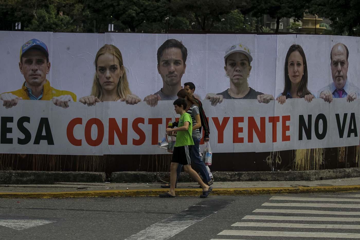 CAR13. CARACAS (VENEZUELA), 24/07/2017.- Transeúntes caminan frente a una valla en rechazo a la Asamblea Constituyente hoy, lunes 24 de julio de 2017, en un colegio electoral de Caracas (Venezuela). Venezuela inicia hoy la semana decisiva para la elección de la Asamblea Nacional Constituyente convocada por el presidente, Nicolás Maduro, con los oficialistas entrando en la recta final de su campaña en medio de protestas y llamados a paro de los opositores en rechazo a esos comicios. EFE/Miguel Gutiérrez