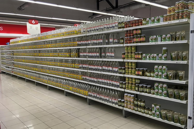 CAR24. CARACAS (VENEZUELA), 24/07/2017.- Personas buscan alimentos en un supermercado con estanterías con alimentos repetidos hoy, lunes 24 de julio de 2017, en Caracas (Venezuela). Numerosos supermercados de Caracas cerrarán hoy con más estanterías vacías de lo habitual después de que los habitantes de la capital hicieran acopio de alimentos y otros productos básicos ante el paro general contra el Gobierno que la oposición convocó para el miércoles y el jueves. EFE/MIGUEL GUTIÉRREZ