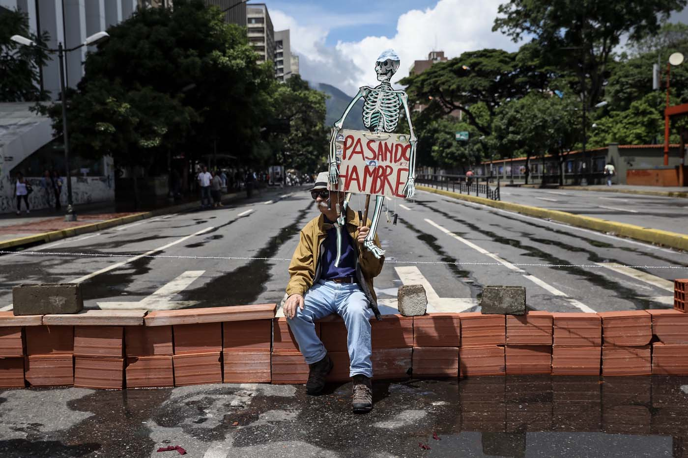 CAR04. CARACAS (VENEZUELA), 28/07/2017.- Un hombre protesta en la calle hoy, viernes 28 de julio de 2017, en Caracas (Venezuela). La oposición venezolana promueve hoy una gran protesta nacional atrancando las calles y avenidas, una convocatoria que reta la prohibición de las autoridades a que se celebre cualquier tipo de reunión pública que perturbe los comicios. EFE/Miguel Gutiérrez