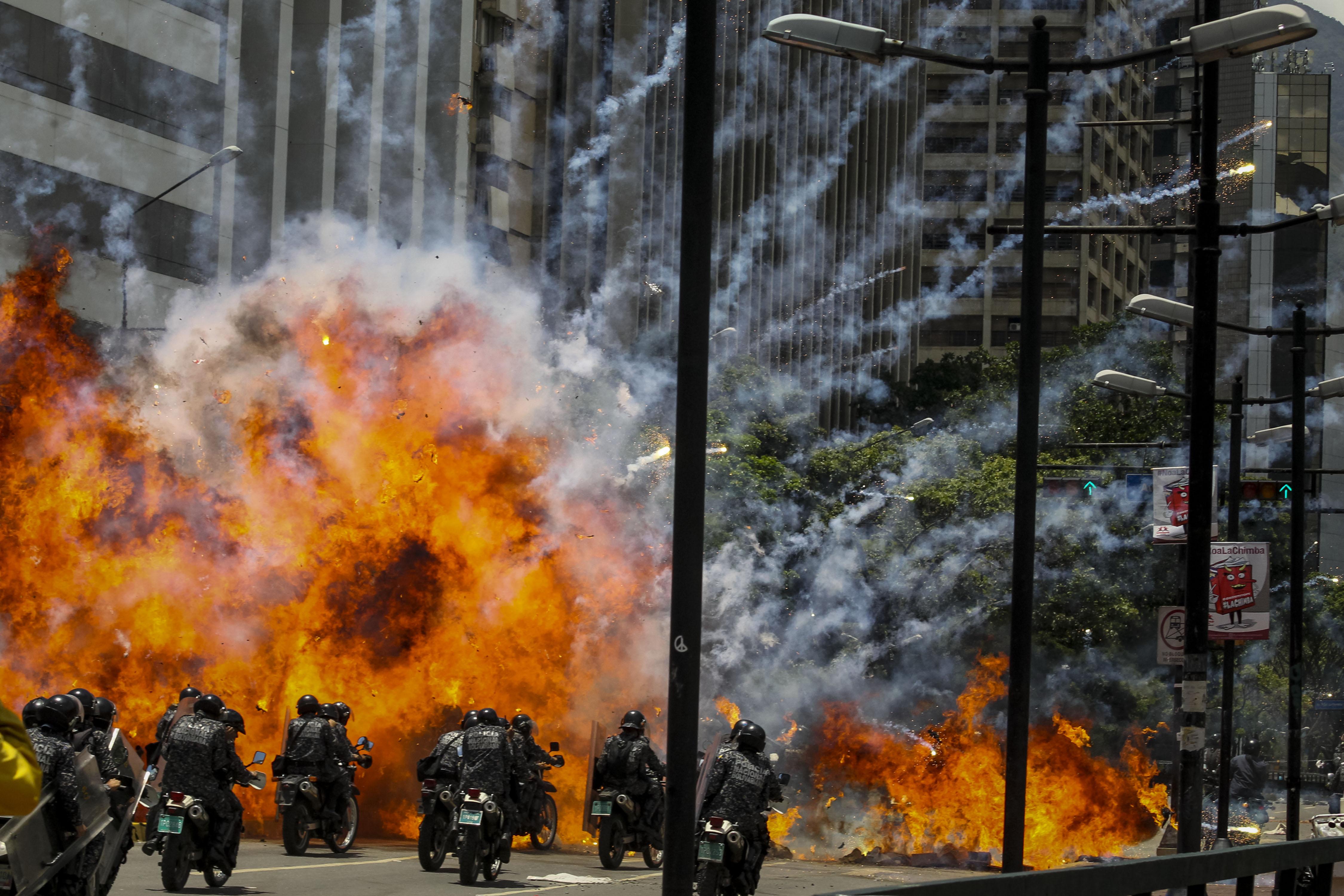 Fotografía de una explosión en medio de varios policías motorizados hoy, domingo 30 de julio de 2017, en inmediaciones de la Plaza Altamira de Caracas (Venezuela). Un agente resultó hoy herido tras la explosión de dos motos de la Policía Nacional Bolivariana (PNB) y otra de un civil, en las inmediaciones de una protesta ciudadana en Caracas contra las elecciones a la Asamblea Nacional Constituyente, convocada por el presidente venezolano, Nicolás Maduro. EFE/Miguel Gutiérrez