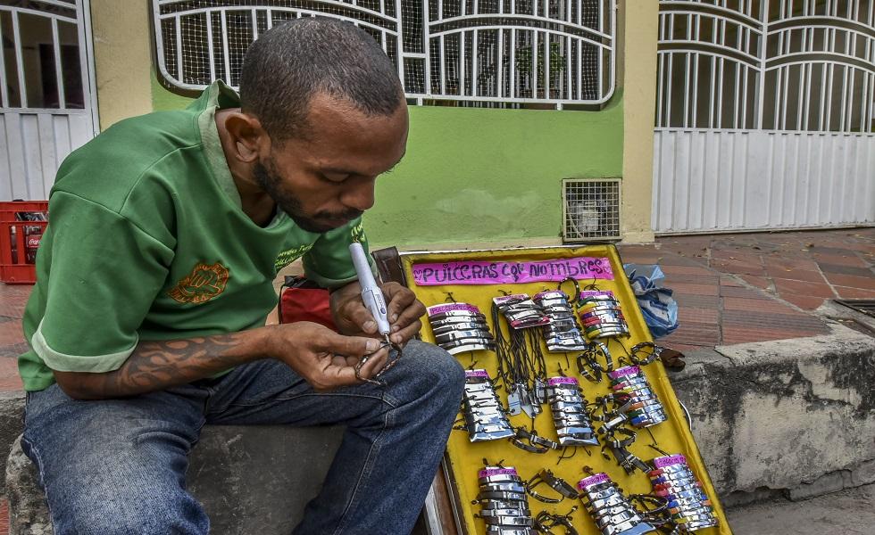 El venezolano Ernesto Toro realiza la venta de brazaletes en espera de comida y refugio frente al Centro de Migración de Cucuta, al norte del departamento de Santander, Colombia, el 26 de julio de 2018. Unos 25.000 venezolanos cruzan a Colombia y regresan a su país diariamente Con alimentos, consumibles y dinero de trabajo ilegal, según fuentes oficiales. Además, hay 47.000 venezolanos en Colombia con estatus migratorio legal y otros 150.000 que ya han completado los 90 días permitidos y ahora están sin visa. Luis Acosta / AFP