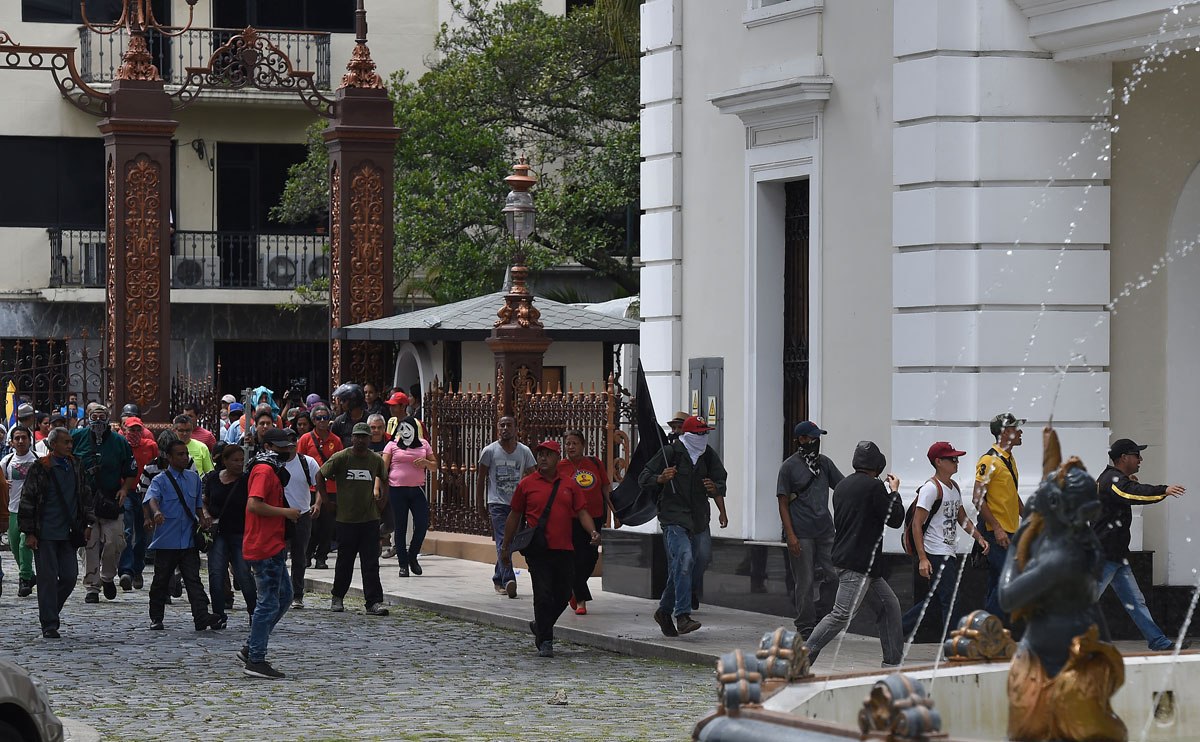 Supporters of Venezuelan President Nicolas Maduro storm the National Assembly building in Caracas on July 5, 2017 as opposition deputies hold a special session on Independence Day. A political and economic crisis in the oil-producing country has spawned often violent demonstrations by protesters demanding President Nicolas Maduro's resignation and new elections. The unrest has left 91 people dead since April 1. / AFP PHOTO / Juan BARRETO