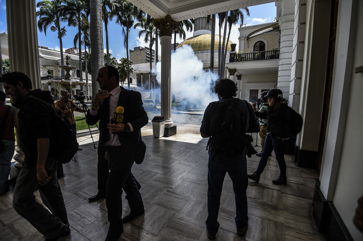 Journalists react as supporters of Venezuelan President Nicolas Maduro storm into the National Assembly building in Caracas on July 5, 2017 as opposition deputies hold a special session on Independence Day. A political and economic crisis in the oil-producing country has spawned often violent demonstrations by protesters demanding President Nicolas Maduro's resignation and new elections. The unrest has left 91 people dead since April 1. / AFP PHOTO / Juan BARRETO