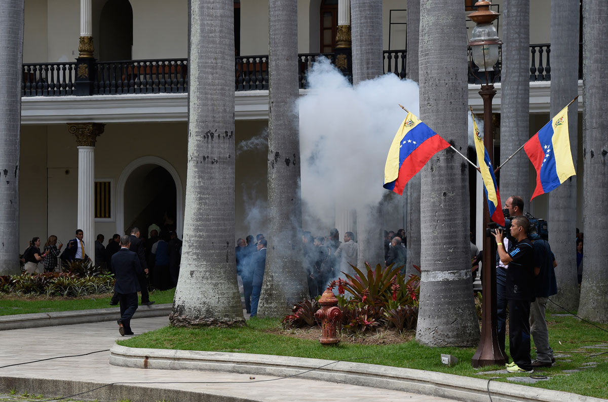 Employees of the National Assembly and members of the press run as Supporters of Venezuelan President Nicolas Maduro storm the building in Caracas on July 5, 2017 as opposition deputies hold a special session on Independence Day. A political and economic crisis in the oil-producing country has spawned often violent demonstrations by protesters demanding President Nicolas Maduro's resignation and new elections. The unrest has left 91 people dead since April 1. / AFP PHOTO / Juan BARRETO
