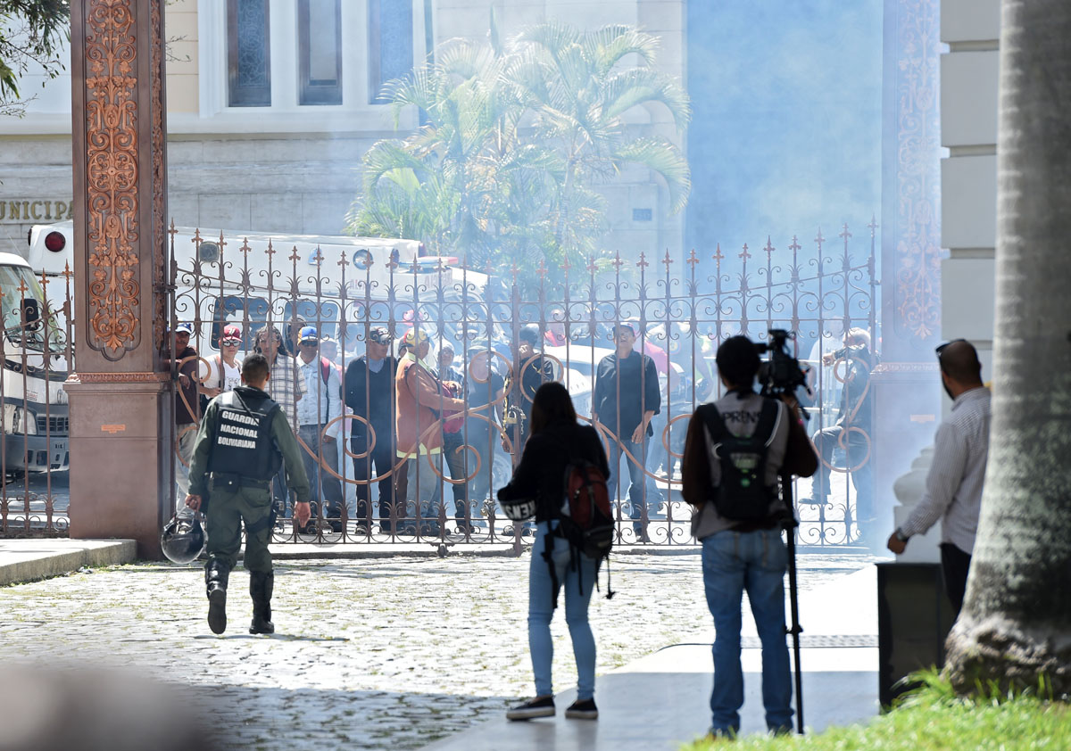 Supporters of Venezuelan President Nicolas Maduro stand at the gate of the National Assembly building in Caracas before storming it on July 5, 2017 as opposition deputies hold a special session on Independence Day. A political and economic crisis in the oil-producing country has spawned often violent demonstrations by protesters demanding President Nicolas Maduro's resignation and new elections. The unrest has left 91 people dead since April 1. / AFP PHOTO / Juan BARRETO