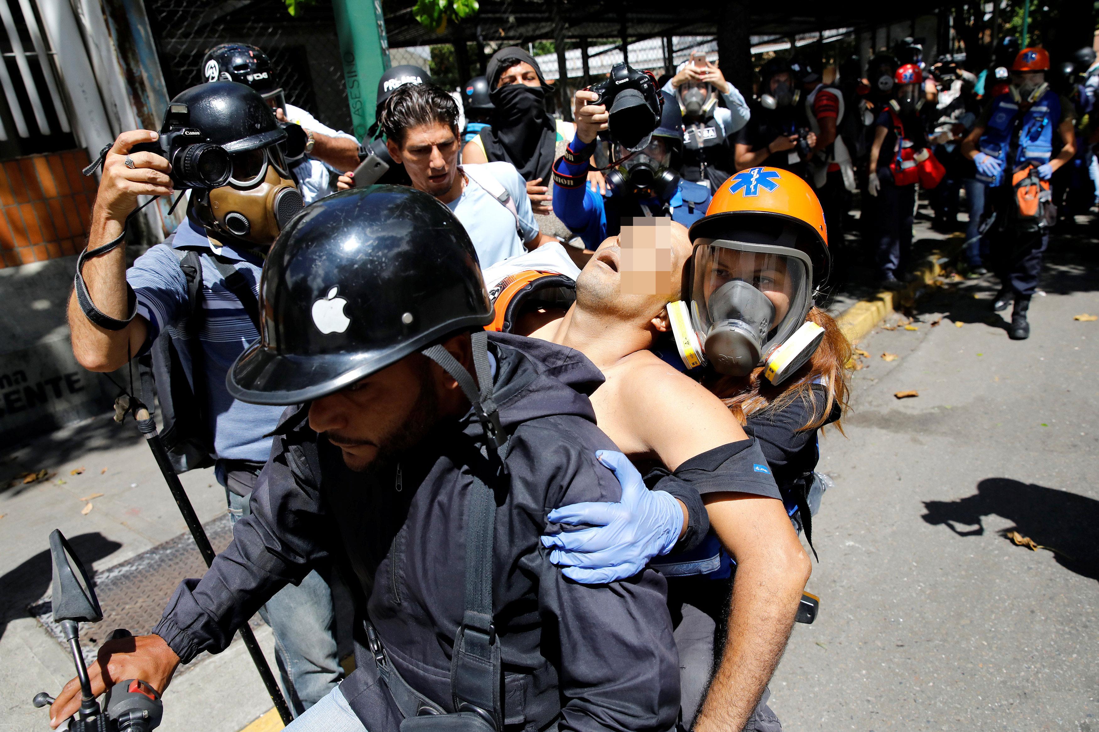 Uno de los heridos tras la brutal represión de este miércoles 26 de julio en Bello Campo es trasladado por paramédicos hacia un centro asistencial. Foto: Reuters