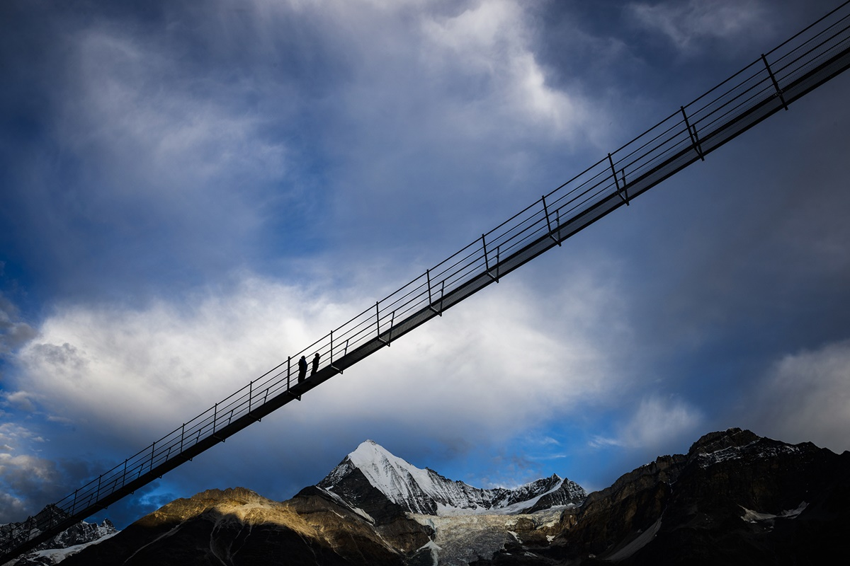 "A couple walks on the ""Europabruecke"",  supposed to be the world's longest pedestrian suspension bridge with a length of 494m, prior to the official inauguration of the construction in Randa, Switzerland, on Saturday, July 29, 2017. The bridge is situated on the Europaweg that connects the villages of Zermatt and Graechen. (Valentin Flauraud/Keystone via AP)"