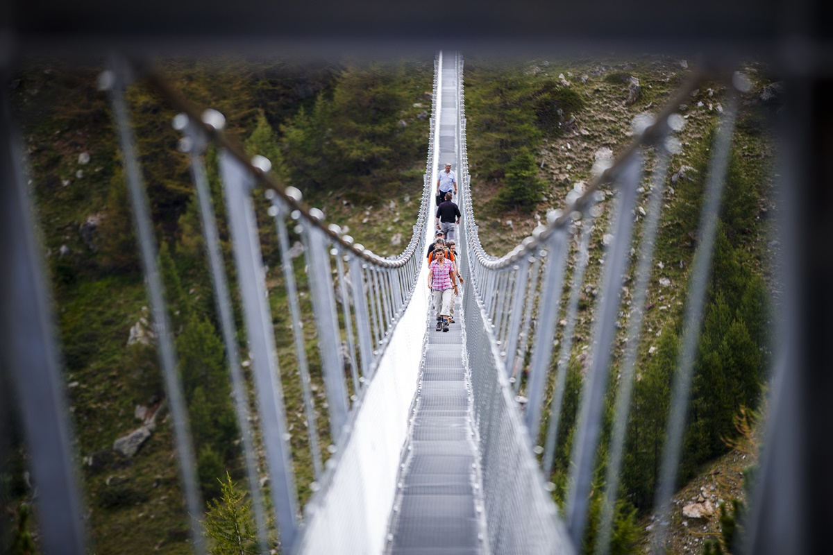 "People walk on the ""Europabruecke"",  supposed to be the world's longest pedestrian suspension bridge with a length of 494m, after the official inauguration of the construction in Randa, Switzerland, on Saturday, July 29, 2017. The bridge is situated on the Europaweg that connects the villages of Zermatt and Graechen. (Valentin Flauraud/Keystone via AP)"