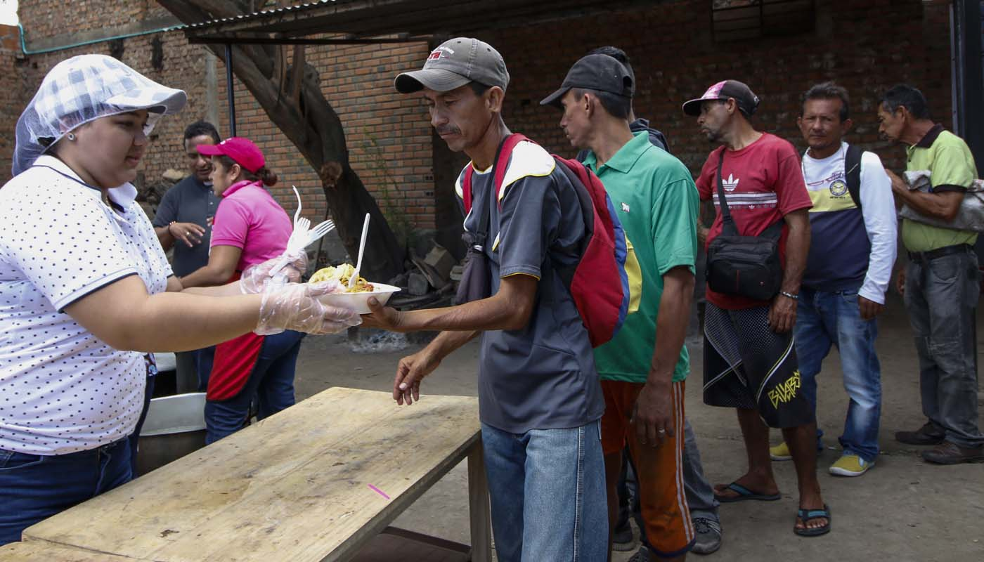 """Venezuelans get food at the Casa de Paso Divina Providencia refuge in Cucuta, Colombia on July 31, 2017. The United States, Mexico, Colombia, Peru and other nations said they did not recognize the results of the election Sunday of a new """"Constituent Assembly"""" superseding Venezuela's legislative body, the opposition-controlled National Assembly. / AFP PHOTO / SCHNEYDER MENDOZA"""