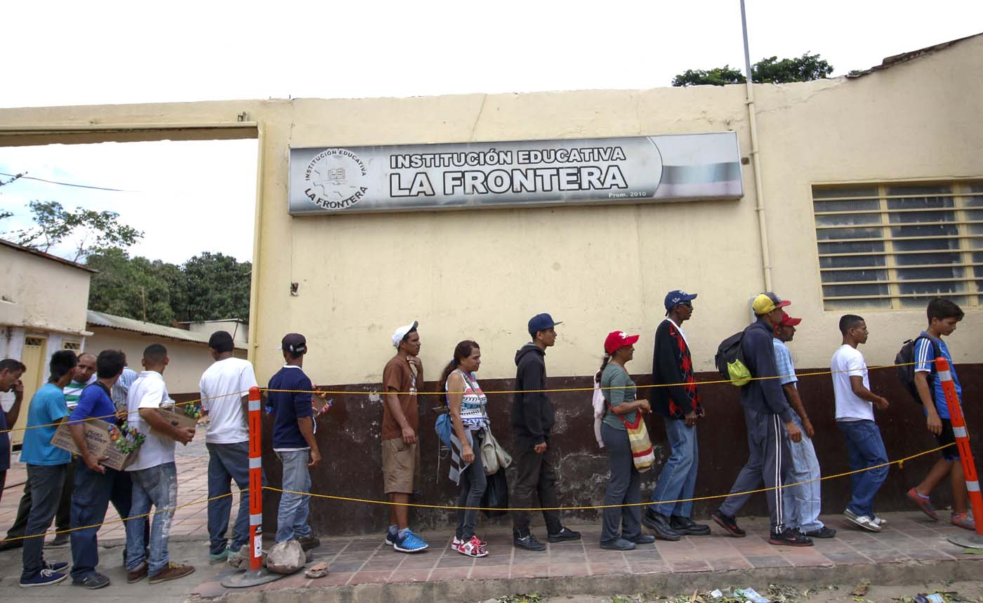 Venezuelans line up to get food at the Casa de Paso Divina Providencia refuge in Cucuta, Colombia on July 31, 2017. after crossed the Simon Bolivar international bridge from San Antonio del Tachira, Venezuela towards Cucuta , who must show the immigration card and the Venezuelan citizenship card to be able to access this assistance,  by different companies and communities in the country / AFP PHOTO / SCHNEYDER MENDOZA