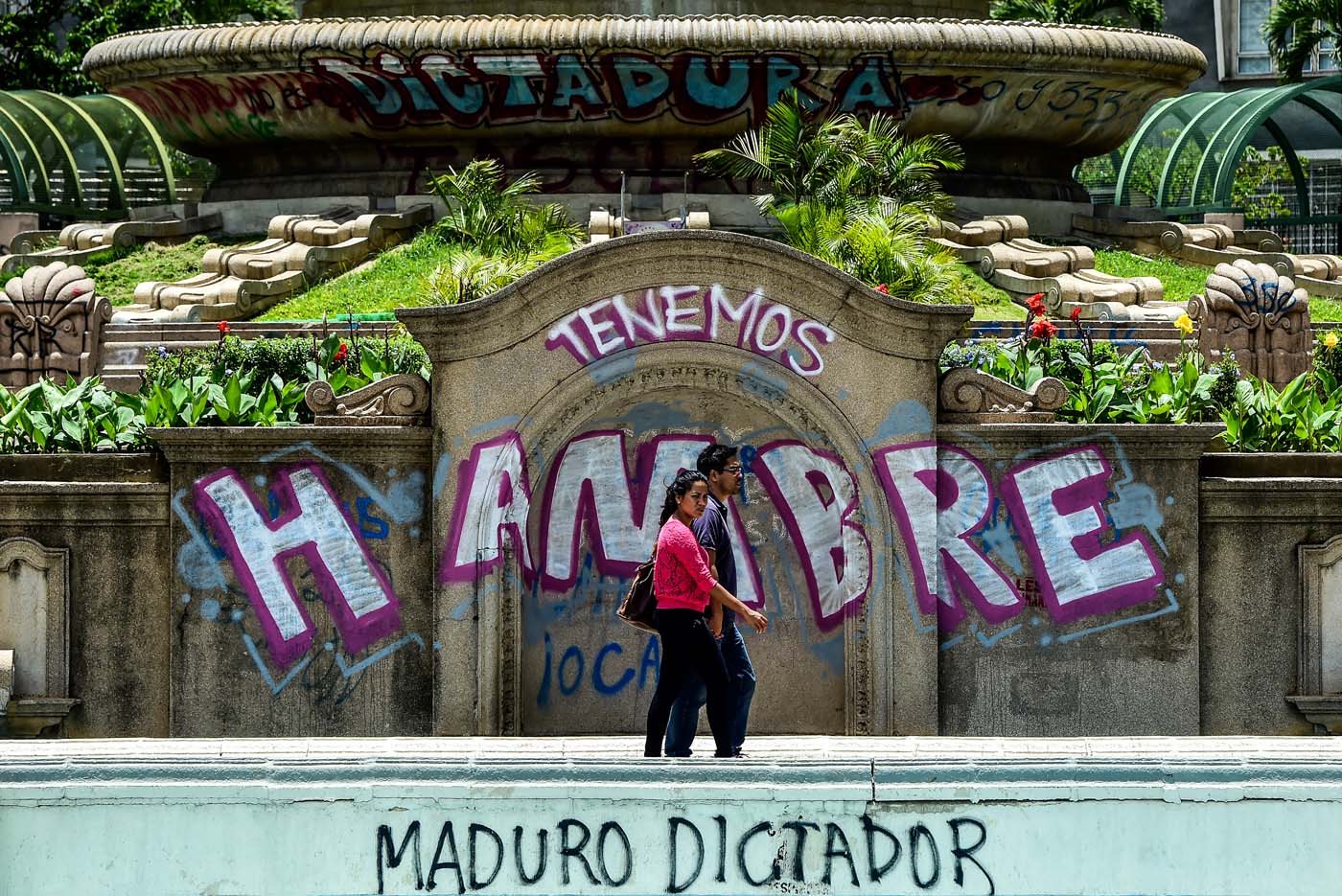 """A couple walks by graffitis reading """"We Are Hungry"""" and """"Maduro Dictator"""" in Caracas on August 8, 2017. Recent demonstrations in Venezuela have stemmed from anger over the installation of an all-powerful Constituent Assembly that many see as a power grab by the unpopular President Nicolas Maduro. The dire economic situation also has stirred deep bitterness as people struggle with skyrocketing inflation and shortages of food and medicine.  / AFP PHOTO / Ronaldo SCHEMIDT"""