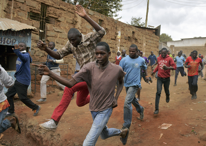Protestors run away after riot police fired live rounds in the Kibera slum in Nairobi, on August 12, 2017. Three people, including a child, have been shot dead in Kenya in opposition protests which raged overnight after the hotly disputed election victory of President Kenyatta. Demonstrations and running battles with police broke out in Nairobi slums after anger in opposition strongholds against an election that losing candidate Raila Odinga claims was massively rigged. / AFP PHOTO / CARL DE SOUZA