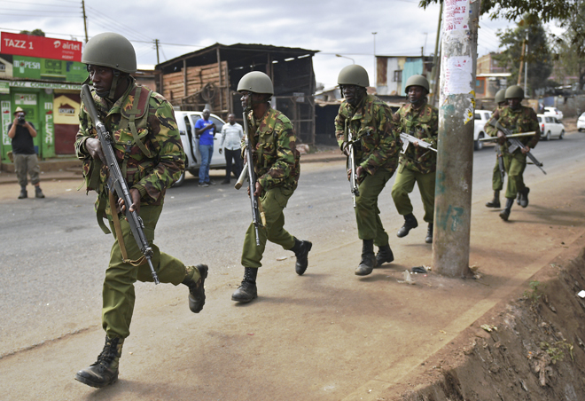 Armed Kenyan police run to disperse protesters in the Kibera slum in Nairobi on August 12, 2017. Three people, including a child, have been shot dead in Kenya during opposition protests which flared for a second day Saturday after the hotly disputed election victory of President Uhuru Kenyatta. Demonstrations and running battles with police broke out in isolated parts of Nairobi slums after anger in opposition strongholds against August 8 election that losing candidate Raila Odinga claims was massively rigged. / AFP PHOTO / CARL DE SOUZA