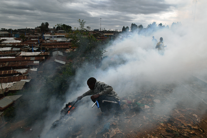 A boy with a stick tries to save belongings from a fire in the Kibera slum in Nairobi on August 12, 2017 Three people, including a child, have been shot dead in Kenya during opposition protests which flared for a second day Saturday after the hotly disputed election victory of President Uhuru Kenyatta. Demonstrations and running battles with police broke out in isolated parts of Nairobi slums after anger in opposition strongholds against August 8 election that losing candidate Raila Odinga claims was massively rigged. / AFP PHOTO / CARL DE SOUZA