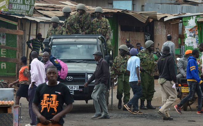 """Kenyan riot police officers patrol on August 12, 2017 in the Kawangware neighborhood of Nairobi.  Eight bodies have been taken to the Nairobi city morgue from three slums which erupted into protests after President Uhuru Kenyatta was declared the victor in a disputed election, a senior police officer said August 12. Seven had sustained gunshot wounds, he said noting the eight bodies came from the Mathare, Kibera and Kawangware areas. """"They have all been taken to the City mortuary,"""" he said, on condition of anonymity.  / AFP PHOTO / STR / SIMON MAINA"""