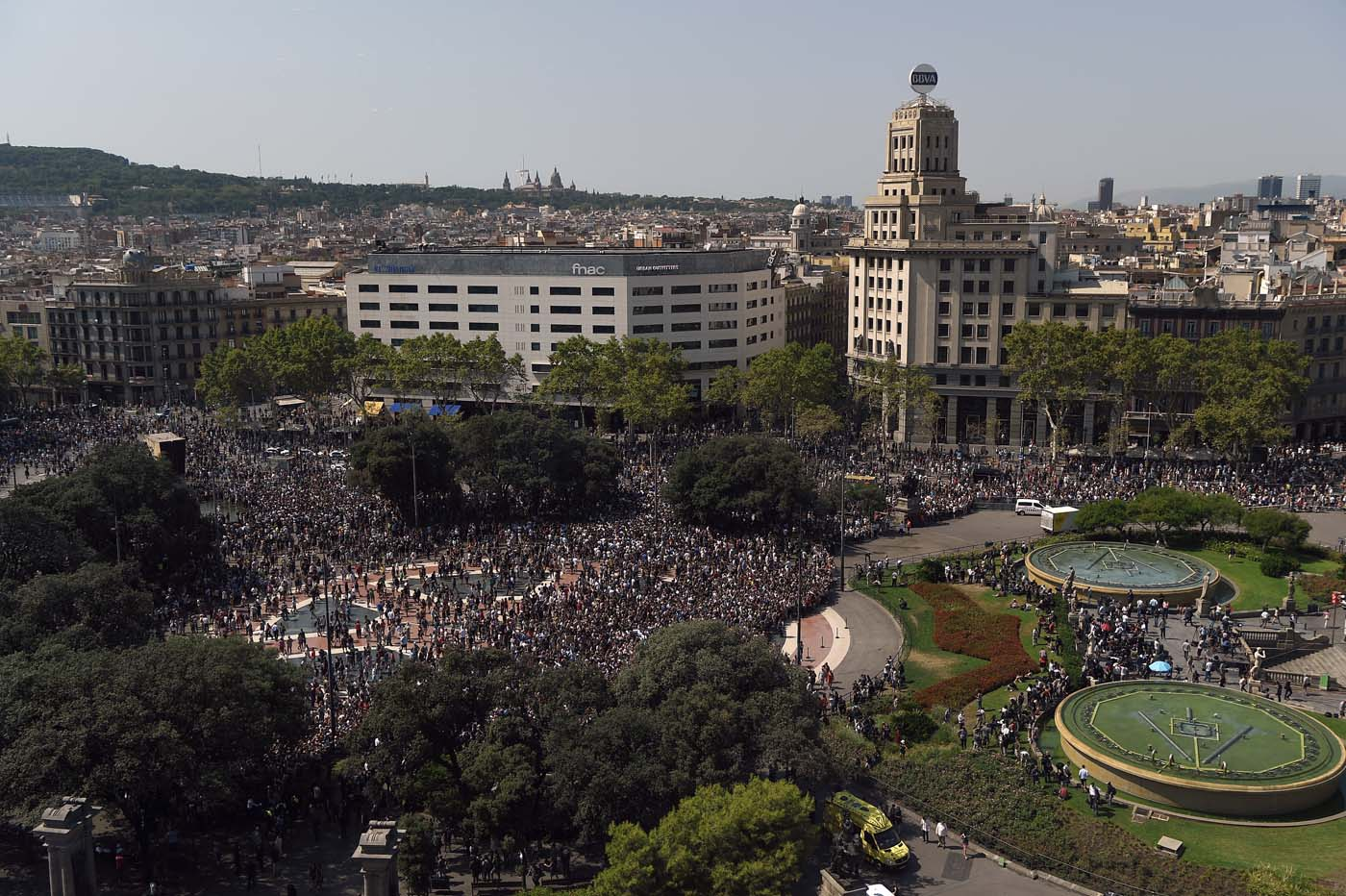 People leave the Plaza de Catalunya after observing a minute of silence for the victims of the Barcelona attack on August 18, 2017, a day after a van ploughed into the crowd, killing 13 persons and injuring over 100 on the Rambla in Barcelona. Drivers have ploughed on August 17, 2017 into pedestrians in two quick-succession, separate attacks in Barcelona and another popular Spanish seaside city, leaving 13 people dead and injuring more than 100 others. In the first incident, which was claimed by the Islamic State group, a white van sped into a street packed full of tourists in central Barcelona on Thursday afternoon, knocking people out of the way and killing 13 in a scene of chaos and horror. Some eight hours later in Cambrils, a city 120 kilometres south of Barcelona, an Audi A3 car rammed into pedestrians, injuring six civilians -- one of them critical -- and a police officer, authorities said. / AFP PHOTO / LLUIS GENE