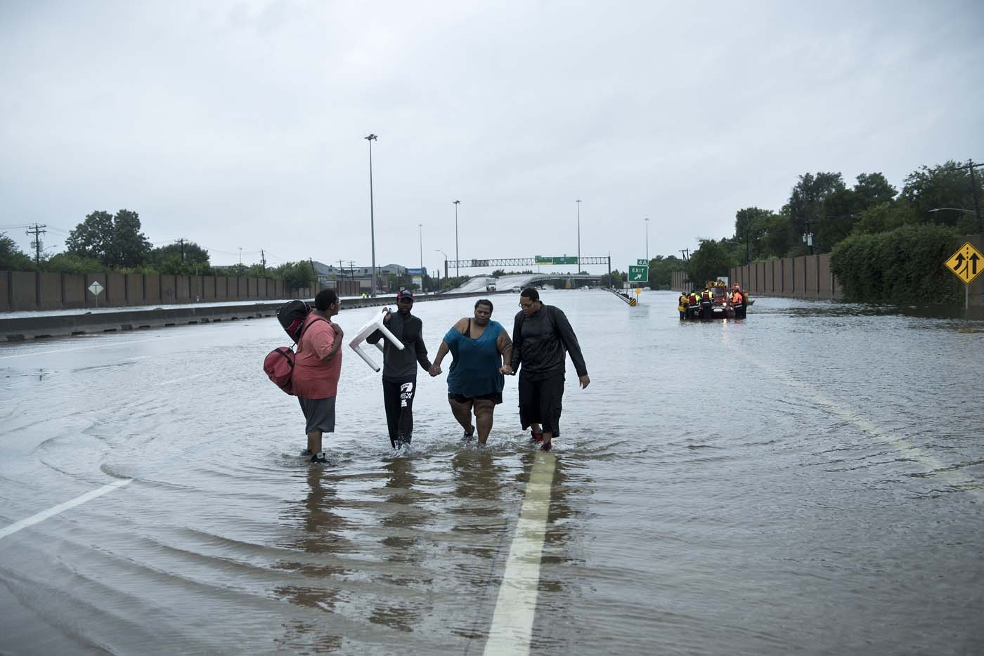 People make their way onto an I-610 overpass after being rescued from flooded homes during the aftermath of Hurricane Harvey August 27, 2017 in Houston, Texas. Hurricane Harvey left a trail of devastation after the most powerful storm to hit the US mainland in over a decade slammed into Texas, destroying homes, severing power supplies and forcing tens of thousands of residents to flee. / AFP PHOTO / Brendan Smialowski