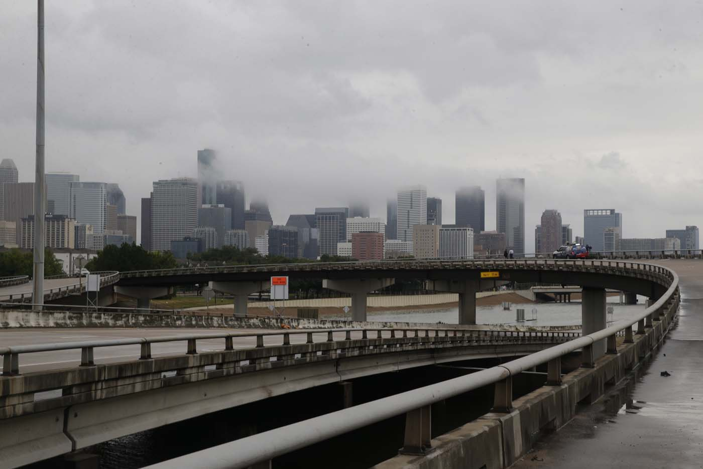 The downtown Houston skyline and flooded highway 288 are seen August 27, 2017 as the city battles with tropical storm Harvey and resulting floods. / AFP PHOTO / Thomas B. Shea
