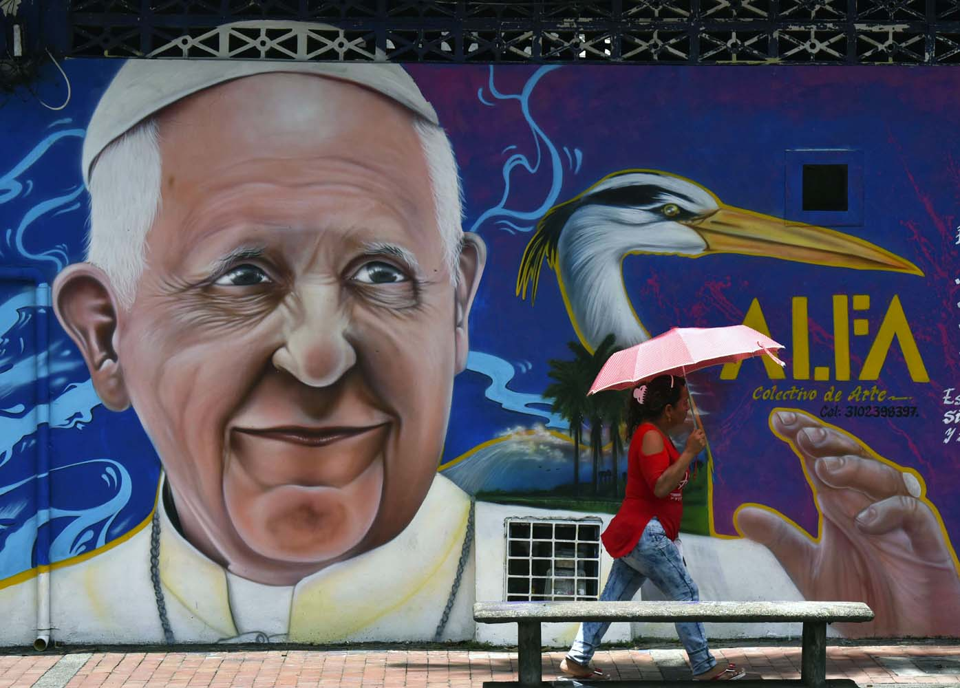 A passer-by walks past a painting of Pope Francis in Villavicencio, Meta, Colombia - where he will give mass during his upcoming visit to Colombia - on August 28, 2017.  Pope Francis will make a special four-day visit to Colombia, from September 6-11, to add his weight to the process of reconciliation between the government and the FARC. / AFP PHOTO / LUIS ACOSTA