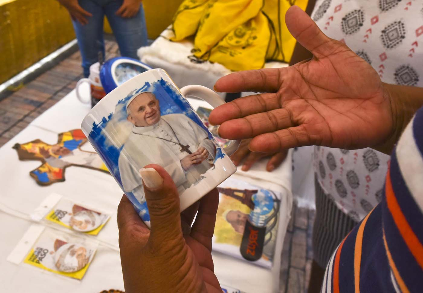 A woman buys a cup with the image of Pope Francis in Villavicencio, Meta, Colombia - where he will give mass during his upcoming visit to Colombia - on August 28, 2017. Pope Francis will make a special four-day visit to Colombia, from September 6-11, to add his weight to the process of reconciliation between the government and the FARC. / AFP PHOTO / LUIS ACOSTA