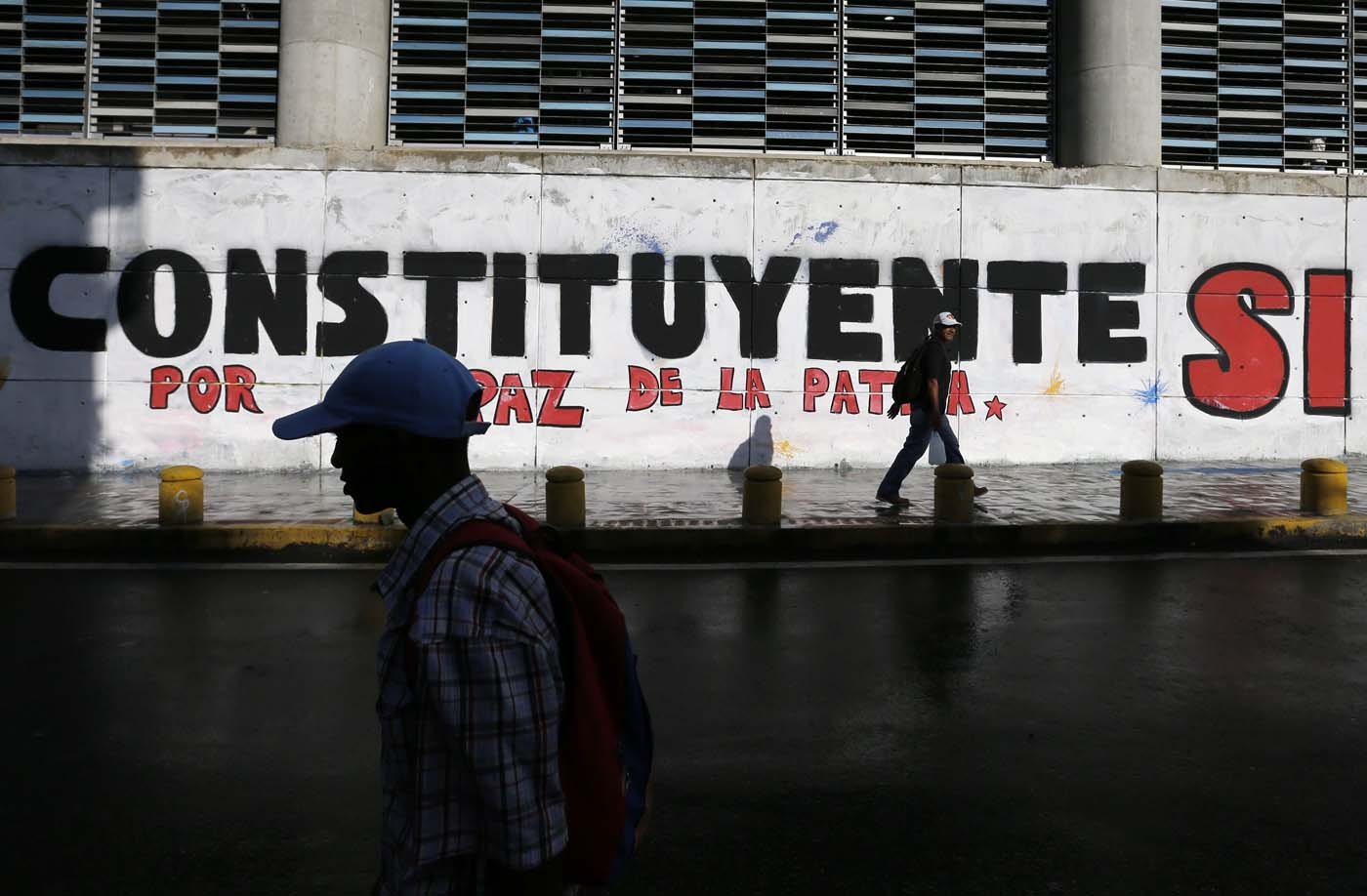People walk by a mural promoting the election during the Constituent Assembly election in Caracas, Venezuela, July 30, 2017. REUTERS/Andres Martinez Casares