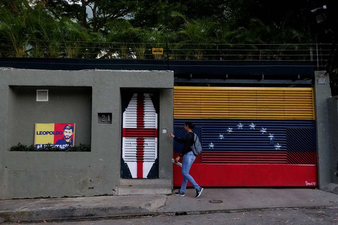 A woman walks in front of the house of Venezuelan opposition leader Leopoldo Lopez in Caracas, Venezuela August 1, 2017. REUTERS/Carlos Garcia Rawlins