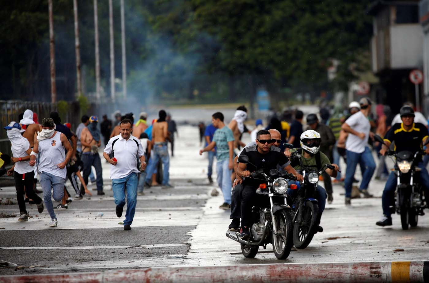 Demonstrators run and ride their motorcycles near Fuerte Paramacay military base during clashes with security forces in Valencia, Venezuela August 6, 2017. REUTERS/Andres Martinez Casares