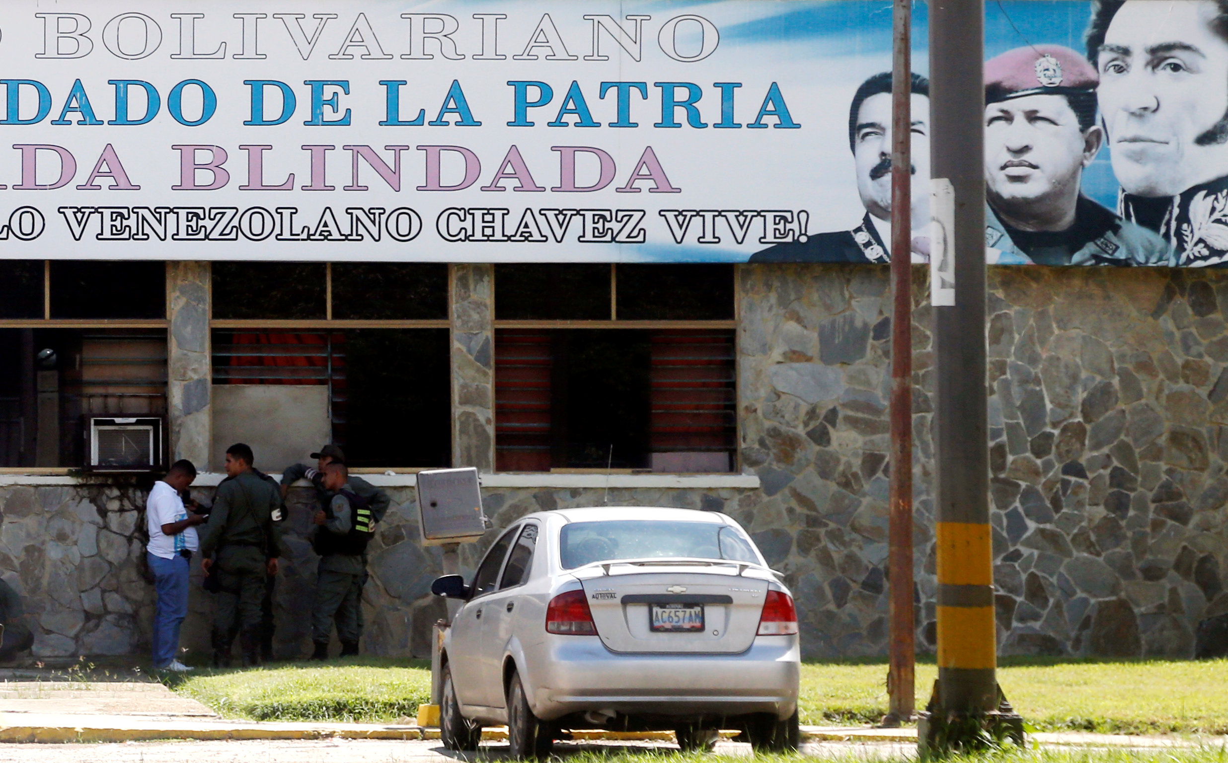 Members of security forces stand beneath a sign with portraits of Venezuela's President Nicolas Maduro, former President Hugo Chavez and Venezuela's national hero Simon Bolivar outside the 41 Brigada Blindada Fuerte Paramacay military base in Valencia, Venezuela August 6, 2017. REUTERS/Andres Martinez Casares
