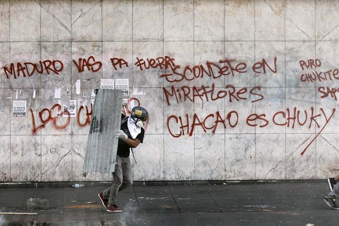 Un manifestante opositor al Gobierno de Venezuela corre en un intento por cubrirse de agentes de la guardia nacional durante una protesta en el distrito de Chacao, en Caracas. Foto de archivo. REUTERS/Christian Verón