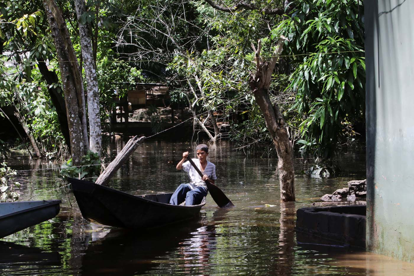 A boy uses a boat to cross through a flooded street in San Felix, Venezuela, August 8, 2017. Picture taken August 8, 2017. REUTERS/William Urdaneta