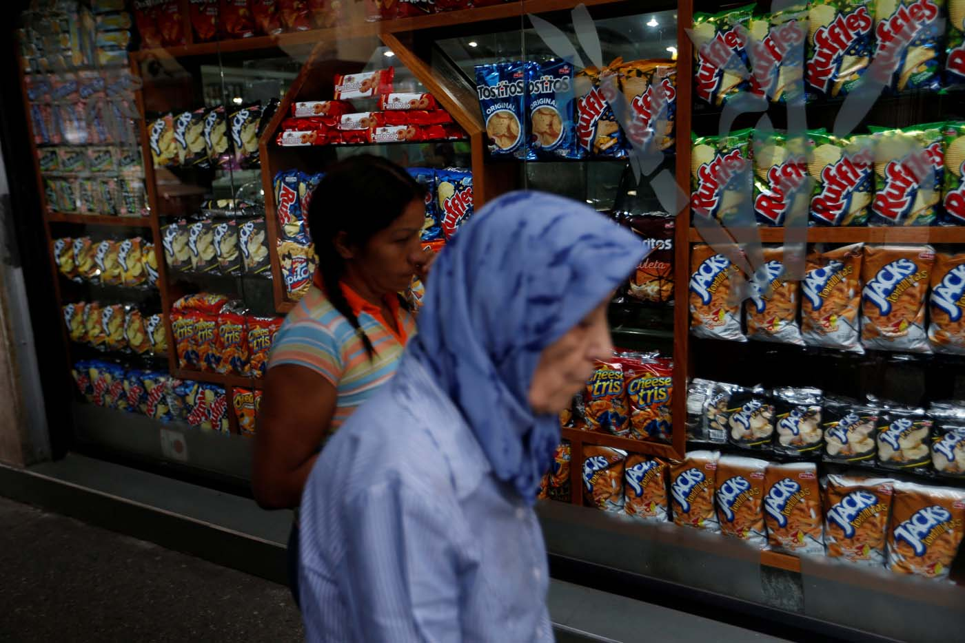 Two women walk past a store in Caracas, Venezuela, August 9, 2017. REUTERS/Andres Martinez Casares