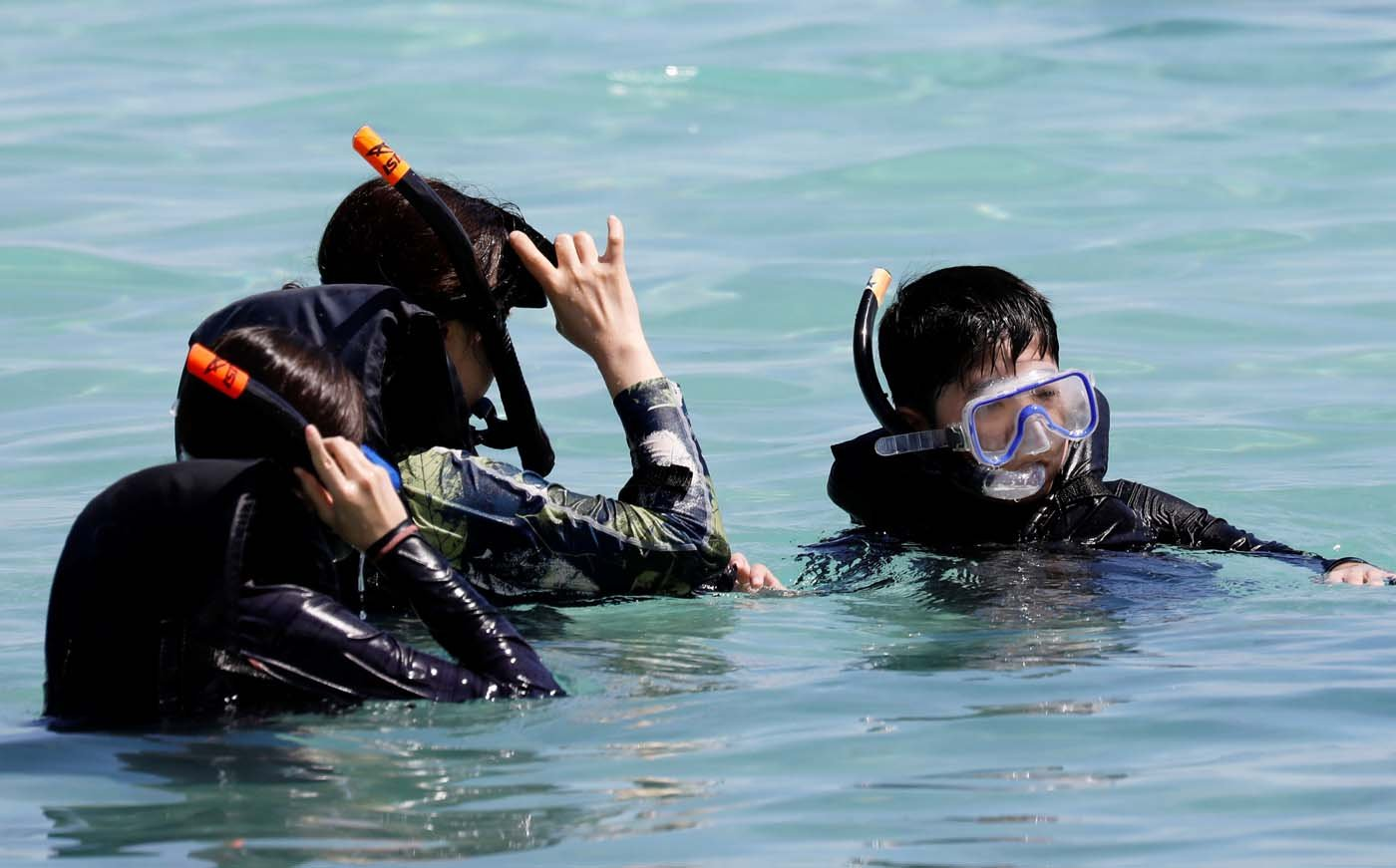 Tourists snorkel on the waters off Tumon beach on the island of Guam, a U.S. Pacific Territory, August 11, 2017. REUTERS/Erik De Castro